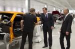 Prime Minister David Cameron meets a member of staff on the McLaren MP4-12C production line